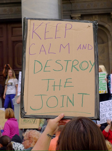 Woman holding cardboard sign that reads 'Destroy the joint